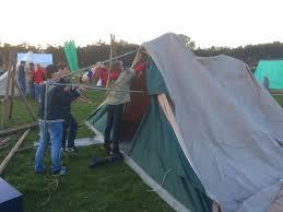 Drie scouts zetten een tent op